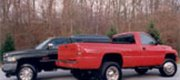 "Dodge Customers Shown: two second generation Dodge trucks, one SRW and one DRW, both shown with Rickson's 19.5"" Black powder coated steel wheels with and without simulators. (SRW shown with now defunct style wheel and cover)."